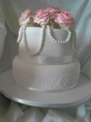 2 tier white wedding cake with lace, roses & pearl trim