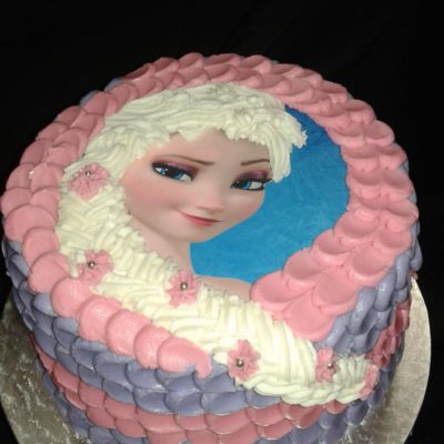Round Frozen theme birthday cake with edible printed topper and frosted braid