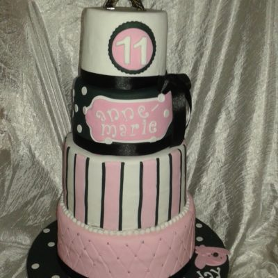 3-tier Paris-theme birthday cake in pink and black with Eiffel Tower topper