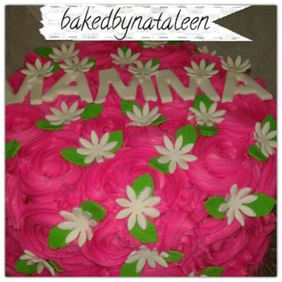 Mother's Day cake with pink frosting roses and white daisies